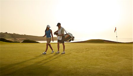 Caddy and woman walking on golf course overlooking ocean Stock Photo - Premium Royalty-Free, Code: 6113-07159212