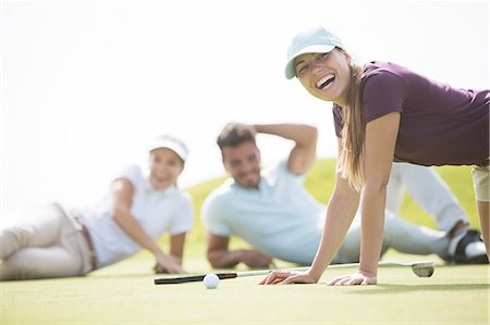 Friends laying and laughing on golf course Stock Photo - Premium Royalty-Free, Code: 6113-07159218