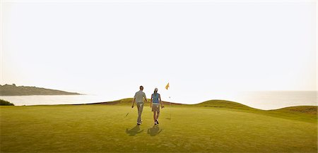 Couple playing golf on course Stock Photo - Premium Royalty-Free, Code: 6113-07159235