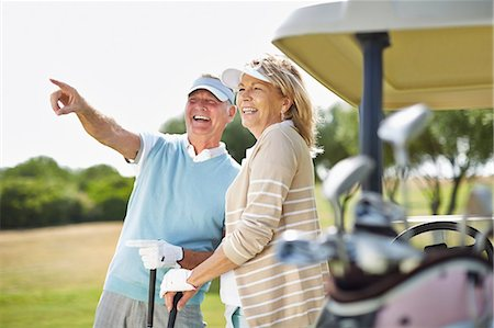 Senior couple standing next to golf cart Stock Photo - Premium Royalty-Free, Code: 6113-07159238