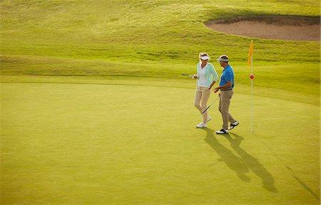 Senior couple walking on golf course Stock Photo - Premium Royalty-Free, Code: 6113-07159300