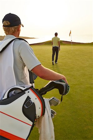 Golfer and caddy nearing golf flag Stock Photo - Premium Royalty-Free, Code: 6113-07159305