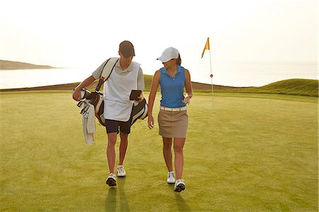 Golfer and caddy walking on golf course Stock Photo - Premium Royalty-Free, Code: 6113-07159306