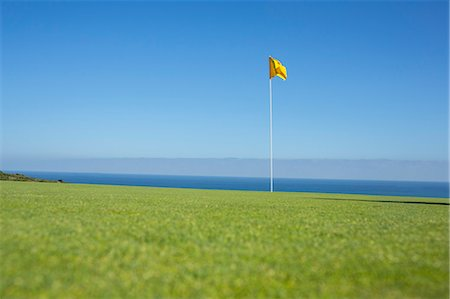Flag on golf course overlooking ocean Stock Photo - Premium Royalty-Free, Code: 6113-07159313