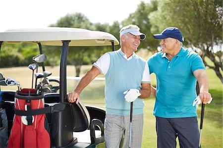 Senior men laughing next to golf cart Stock Photo - Premium Royalty-Free, Code: 6113-07159311