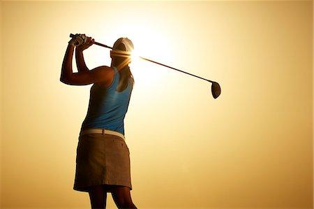 swing (sports) - Sun shining behind woman swinging golf club Stock Photo - Premium Royalty-Free, Code: 6113-07159318