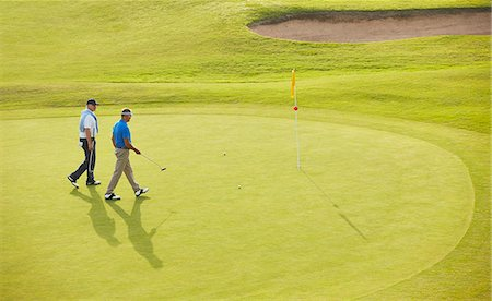 Senior men walking toward flag and hole on golf course Stock Photo - Premium Royalty-Free, Code: 6113-07159322