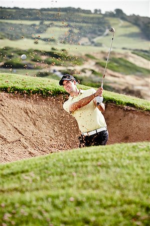 Man swinging from sand trap on golf course Stock Photo - Premium Royalty-Free, Code: 6113-07159324