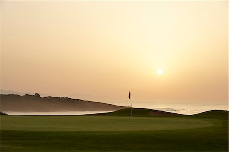 Sunset over ocean and golf course Stock Photo - Premium Royalty-Free, Code: 6113-07159330
