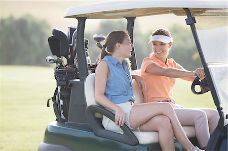 Women driving cart on golf course Stock Photo - Premium Royalty-Free, Code: 6113-07159335