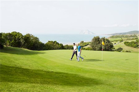 Men walking on golf course overlooking ocean Stock Photo - Premium Royalty-Free, Code: 6113-07159336