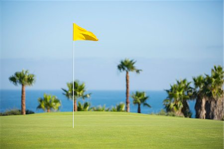 Flag in hole on golf course overlooking ocean Stock Photo - Premium Royalty-Free, Code: 6113-07159339