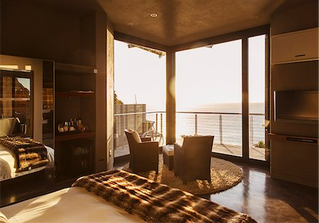Luxury bedroom overlooking ocean at sunset Stock Photo - Premium Royalty-Free, Code: 6113-07159474