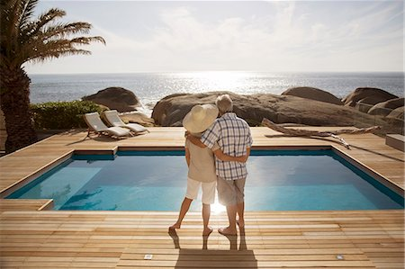 people and vacation - Senior couple hugging by modern pool overlooking ocean Stock Photo - Premium Royalty-Free, Code: 6113-07159487