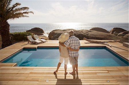 Senior couple hugging by modern pool overlooking ocean Stock Photo - Premium Royalty-Free, Code: 6113-07159487