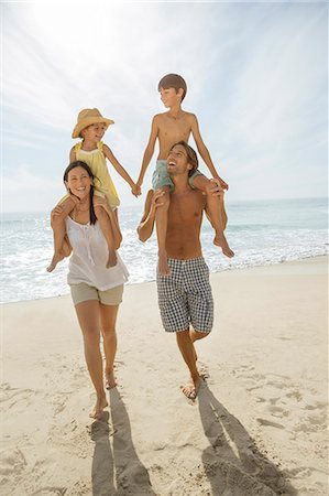 Parents carrying children on shoulders at beach Stock Photo - Premium Royalty-Free, Code: 6113-07159548
