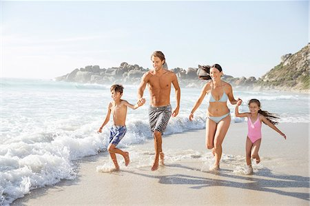 preteen beach - Family running together in waves Stock Photo - Premium Royalty-Free, Code: 6113-07159564