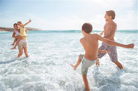 preteen girl topless - Family playing together in waves on beach Stock Photo - Premium Royalty-Free, Code: 6113-07159568