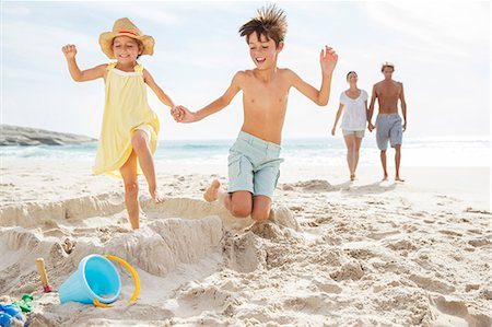 Children kicking down sandcastle on beach Stock Photo - Premium Royalty-Free, Code: 6113-07159586