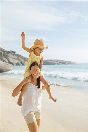 Mother carrying daughter on shoulders on beach Stock Photo - Premium Royalty-Free, Code: 6113-07159589