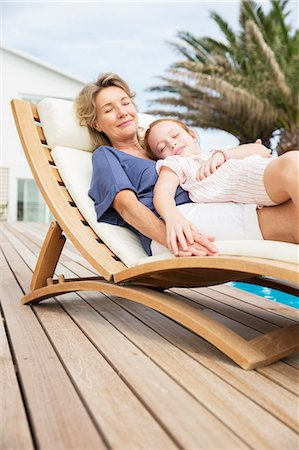 Older woman and granddaughter relaxing in lawn chair Stock Photo - Premium Royalty-Free, Code: 6113-07159593