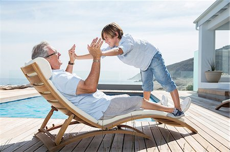 rich lifestyle - Grandfather and grandson playing at poolside Stock Photo - Premium Royalty-Free, Code: 6113-07159507