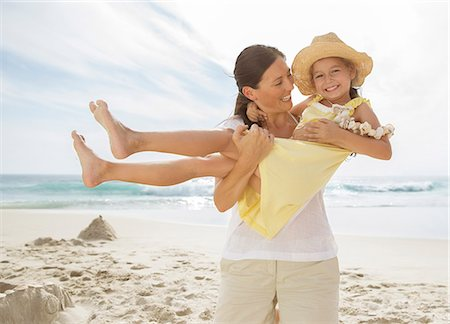 Mother holding daughter on beach Stock Photo - Premium Royalty-Free, Code: 6113-07159512