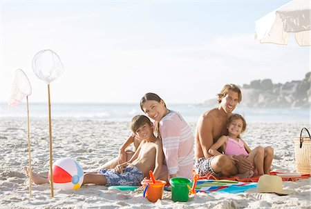 preteen girl topless - Family relaxing together on beach Stock Photo - Premium Royalty-Free, Code: 6113-07159515