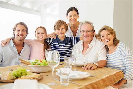 Multi-generation family smiling together at table Stock Photo - Premium Royalty-Free, Code: 6113-07159526