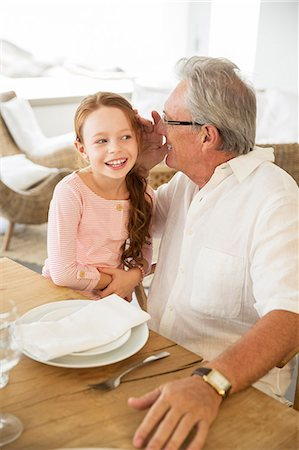 Older man and granddaughter whispering at table Stock Photo - Premium Royalty-Free, Code: 6113-07159647