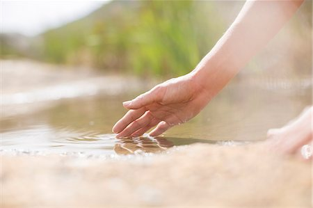 female hand - Woman dipping fingers in rural pond Stock Photo - Premium Royalty-Free, Code: 6113-07159675
