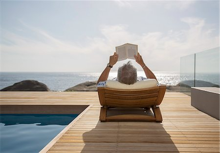 Older man reading by pool Stock Photo - Premium Royalty-Free, Code: 6113-07159685