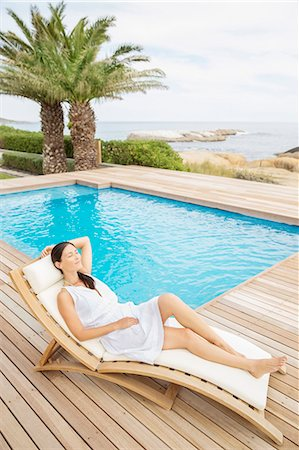 Woman relaxing by pool Stock Photo - Premium Royalty-Free, Code: 6113-07159689
