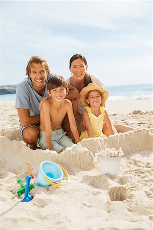 preteen beach - Family sitting in sandcastle on beach Stock Photo - Premium Royalty-Free, Code: 6113-07159605