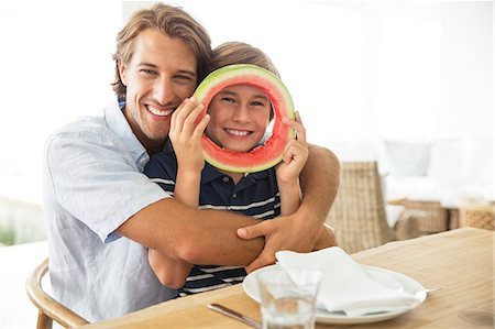 Father and son playing with food at table Stock Photo - Premium Royalty-Free, Code: 6113-07159630