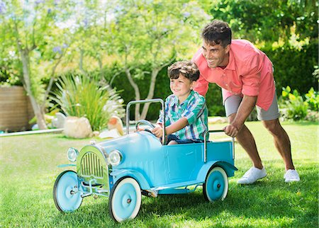 pushing - Father and son playing in backyard Stock Photo - Premium Royalty-Free, Code: 6113-07159749