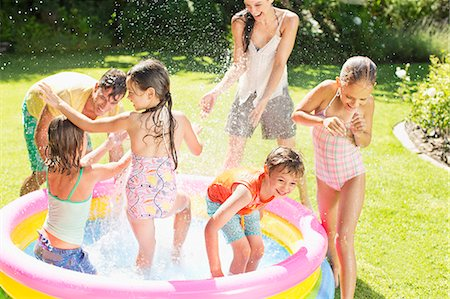 Family playing in paddling pool in backyard Stock Photo - Premium Royalty-Free, Code: 6113-07159703