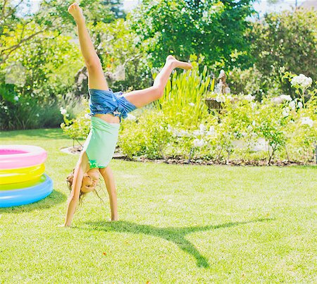 playing - Girl doing cartwheels in backyard Stock Photo - Premium Royalty-Free, Code: 6113-07159720