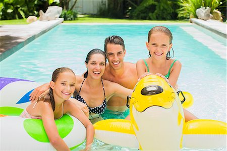 Family swimming in pool together Stock Photo - Premium Royalty-Free, Code: 6113-07159722