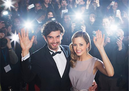 Celebrity couple waving on red carpet with paparazzi in background Stock Photo - Premium Royalty-Free, Code: 6113-07159890