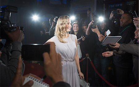 Female celebrity posing for paparazzi on red carpet Stock Photo - Premium Royalty-Free, Code: 6113-07159892