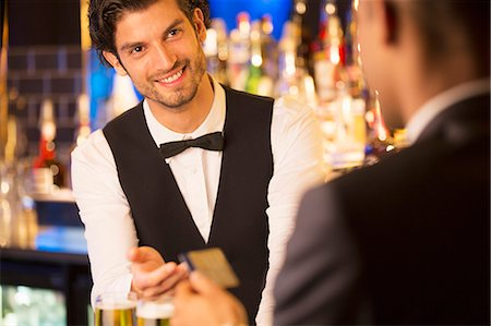 Well dressed bartender taking credit card from customer in luxury bar Stock Photo - Premium Royalty-Free, Code: 6113-07159945