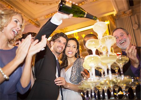 Well dressed couple pouring champagne pyramid Stock Photo - Premium Royalty-Free, Code: 6113-07159952