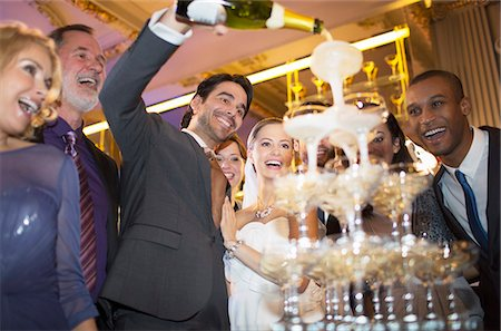 Groom pouring champagne pyramid at wedding reception Stock Photo - Premium Royalty-Free, Code: 6113-07159954
