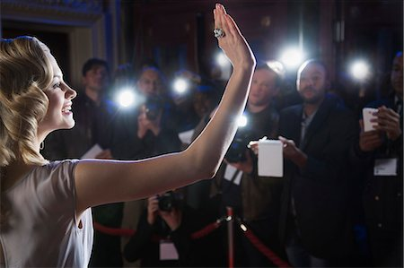 Female celebrity waving to paparazzi at red carpet event Stock Photo - Premium Royalty-Free, Code: 6113-07159959