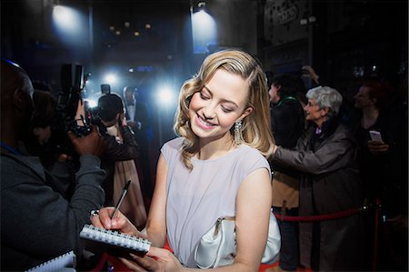 Well dressed female celebrity signing autographs at red carpet event Stock Photo - Premium Royalty-Free, Code: 6113-07159963