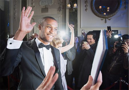 Well dressed male celebrity waving to fans and paparazzi at red carpet event Stock Photo - Premium Royalty-Free, Code: 6113-07159962