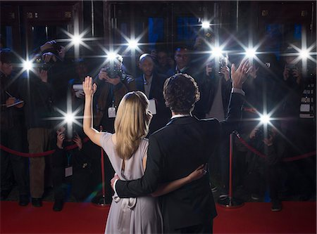 Rear view of celebrity couple waving to paparazzi at red carpet event Stock Photo - Premium Royalty-Free, Code: 6113-07159993
