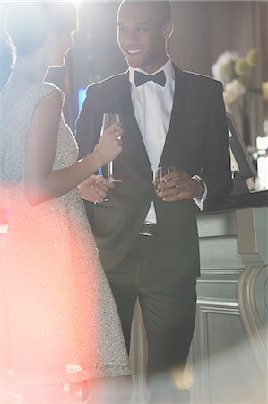 Well dressed couple talking and drinking champagne and cocktail Stock Photo - Premium Royalty-Free, Code: 6113-07159907