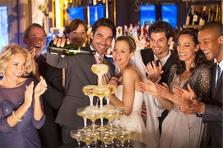 Bride and group pouring champagne pyramid at wedding reception Stock Photo - Premium Royalty-Free, Code: 6113-07159904